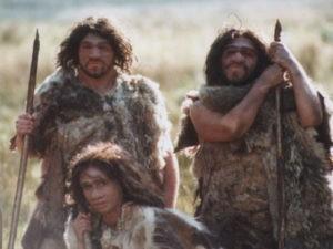 На фото первобытные люди в плащах из шкур животных